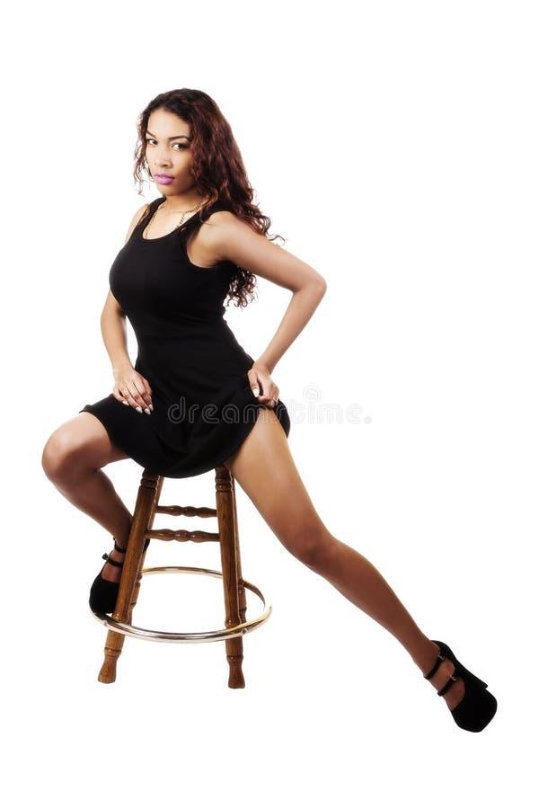 Jeune femme hispanique attirante s'asseyant dans la robe noire photographie stock