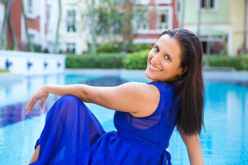 Jeune femme hispanique dans la robe bleue détendant par la piscine image stock