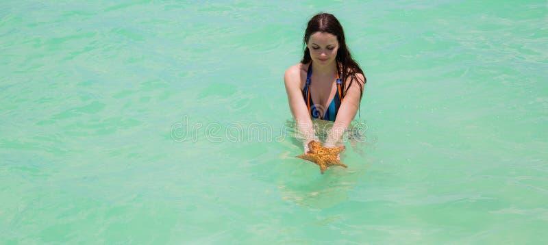 Jeune femme humide avec de longs cheveux superbes dans étoiles de mer de retenue d'eau de mer de turquoise de grandes dans des ma image libre de droits