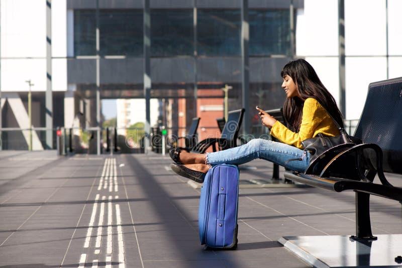 Jeune femme indienne de sourire s'asseyant à la station avec des sacs et à regarder le téléphone portable photo stock