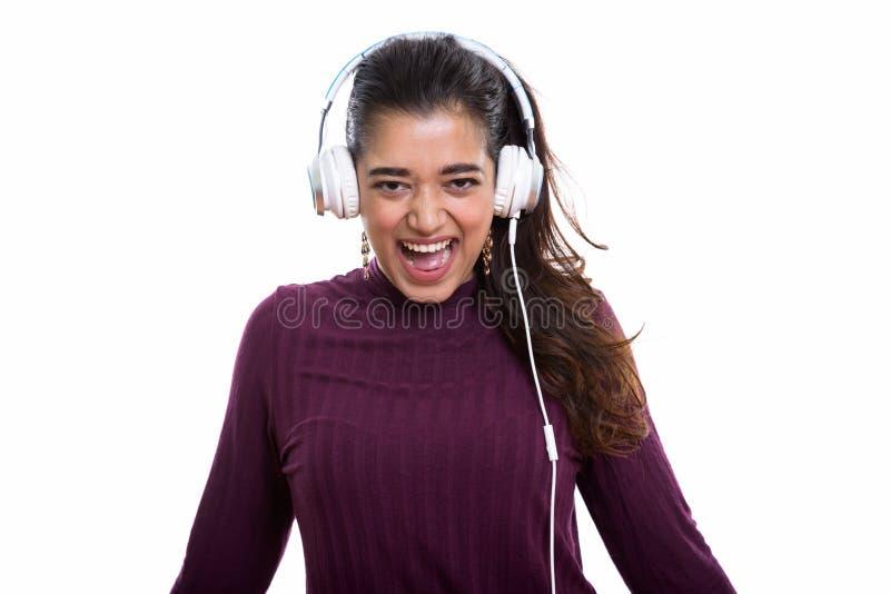 Jeune femme indienne heureuse souriant et criant tout en écoutant photo libre de droits
