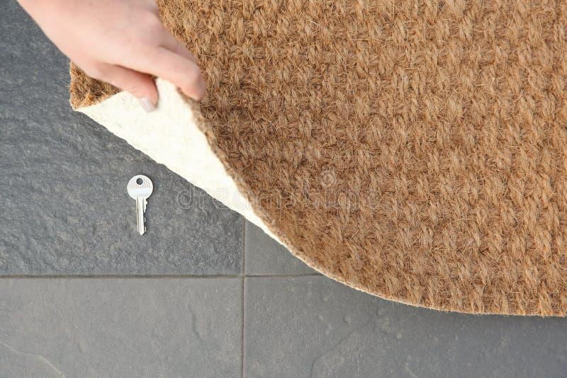 Jeune femme indiquant la clé cachée sous le tapis de porte, vue supérieure image stock