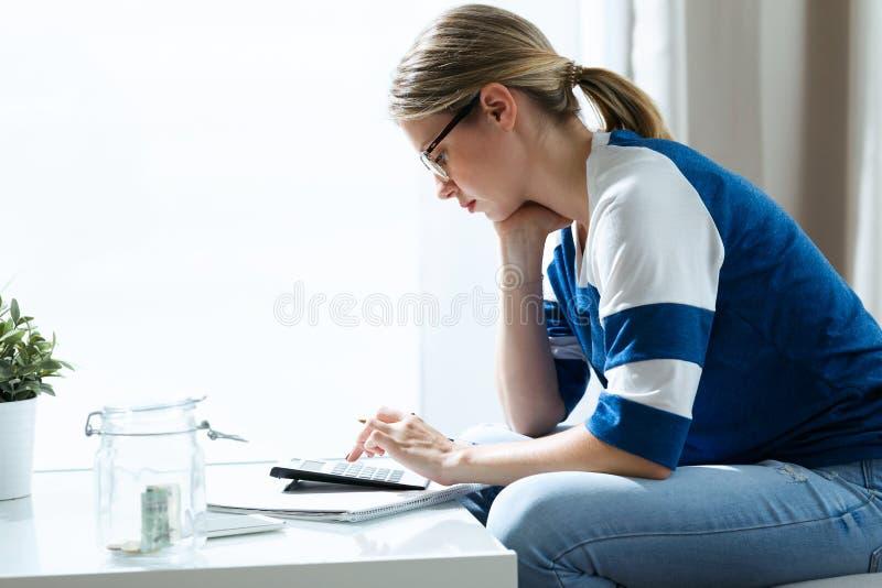 Jeune femme inquiétée à l'aide de la calculatrice et comptant son épargne tout en se reposant sur le sofa à la maison images libres de droits