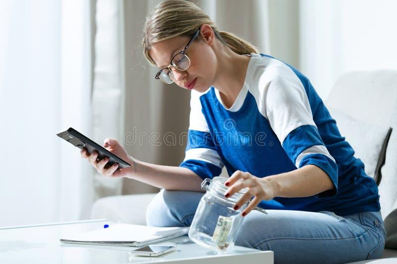 Jeune femme inquiétée à l'aide de la calculatrice et regardant son épargne tout en se reposant sur le sofa à la maison photo stock