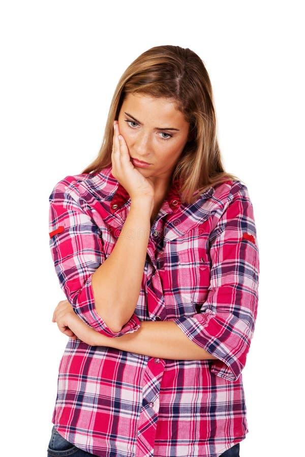 Jeune femme inquiétée avec la main sur la joue photographie stock libre de droits