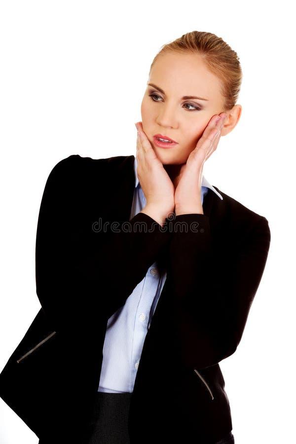 Jeune femme inquiétée d'affaires avec des mains sur des joues images stock