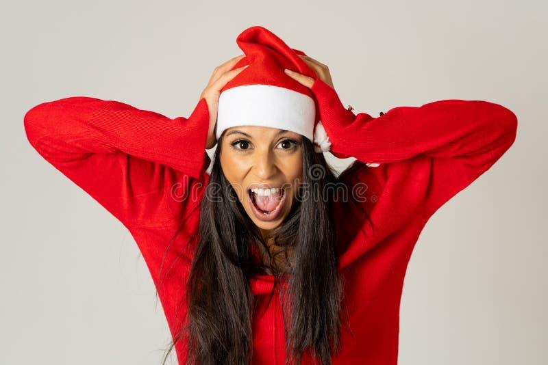 Jeune femme inquiétée dans le chapeau du père noël criant dans l'effort manquant d'heure pour Noël image stock