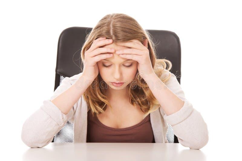 Jeune femme inquiétée s'asseyant au bureau photographie stock libre de droits