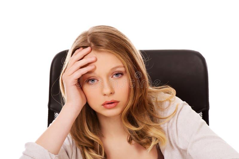 Jeune femme inquiétée s'asseyant au bureau images libres de droits