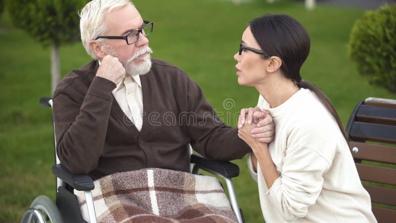 Jeune femme inquiétée soulageant le grand-père malade s'asseyant dans le fauteuil roulant, hôpital photos stock