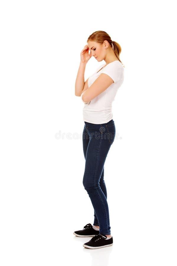 Jeune femme inquiétée touchant sa tête images stock
