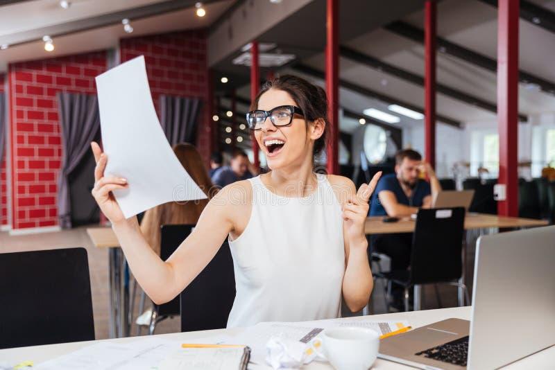 Jeune femme inspirée de sourire faisant le plan d'action dans le bureau image libre de droits