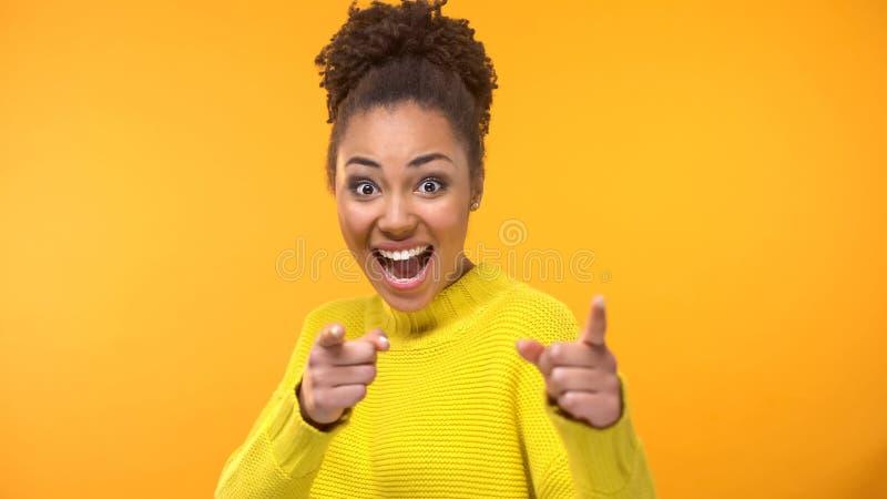 Jeune femme inspirée dirigeant des mains in camera sur le fond jaune, motivation photo libre de droits