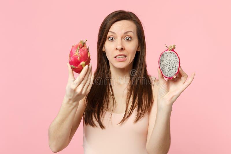 Jeune femme intéressée tenant les halfs disponibles du pitahaya mûr frais, fruit du dragon d'isolement sur le fond en pastel rose photo libre de droits