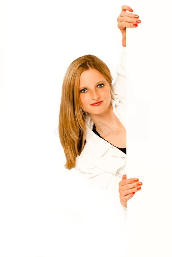 Jeune femme jetant un coup d'oeil autour du coin image stock