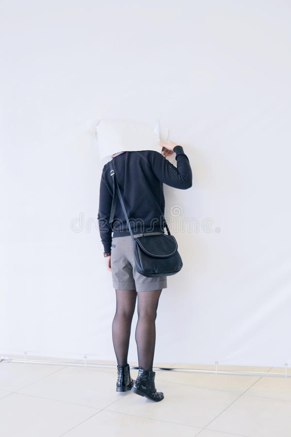 Jeune femme jetant un coup d'oeil par le trou dans le mur de papier photos stock