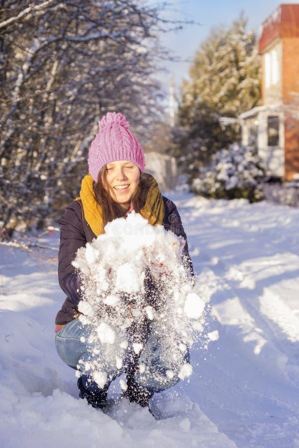 Jeune femme jouant avec la neige en hiver images stock