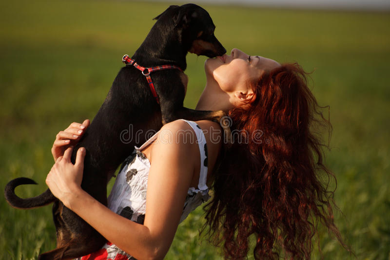 Jeune femme jouant avec son chien photo stock