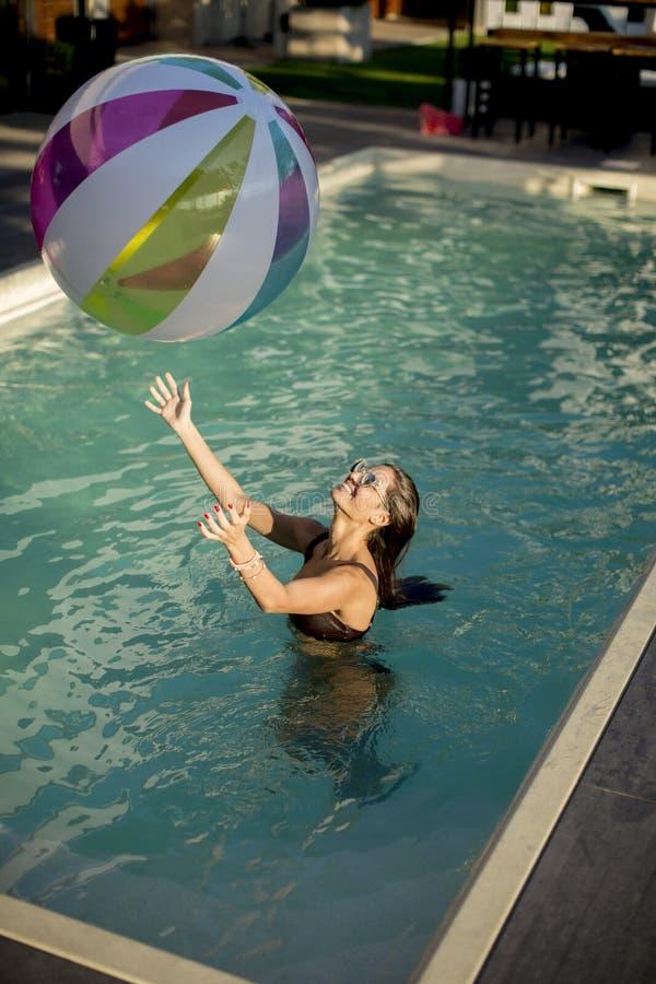 Jeune femme jouant avec une boule dans la piscine image libre de droits