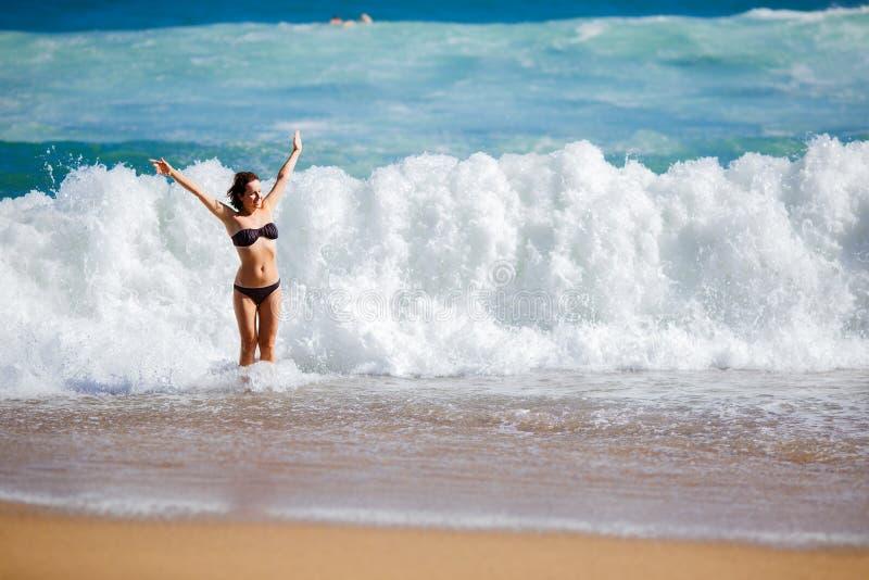 Jeune femme jouant dans de grandes vagues photos libres de droits