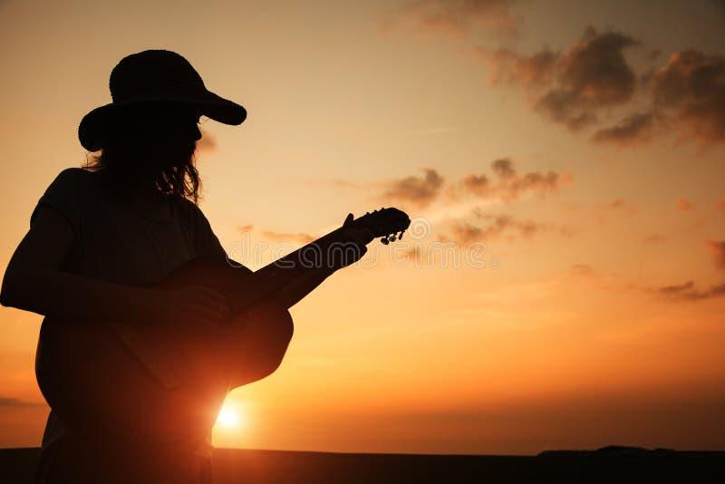 jeune femme jouant la guitare au coucher du soleil photographie stock