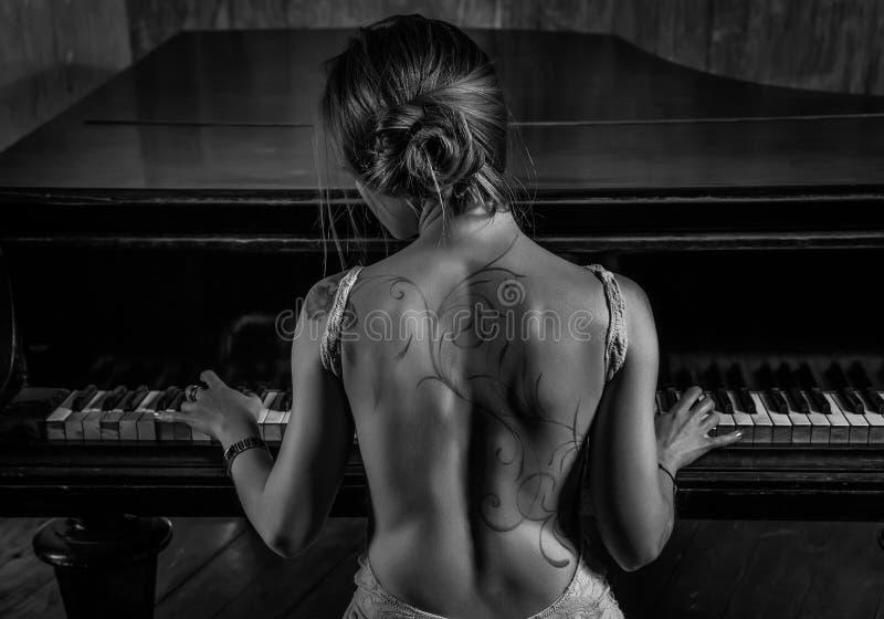 Jeune femme jouant le piano photo stock