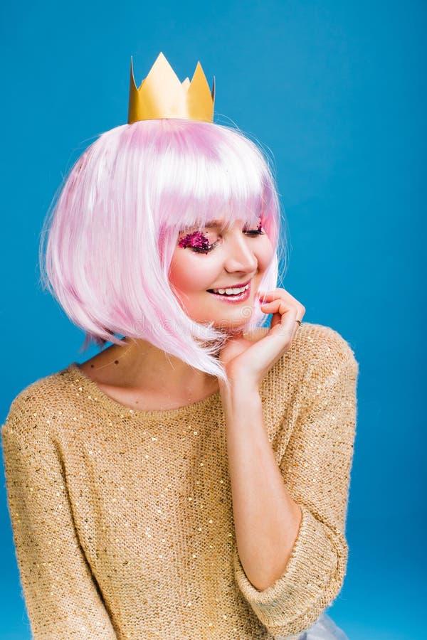 Jeune femme joyeuse à la mode de portrait avec les cheveux roses coupés sur le fond bleu Souriant avec les yeux fermés, brightful photo stock
