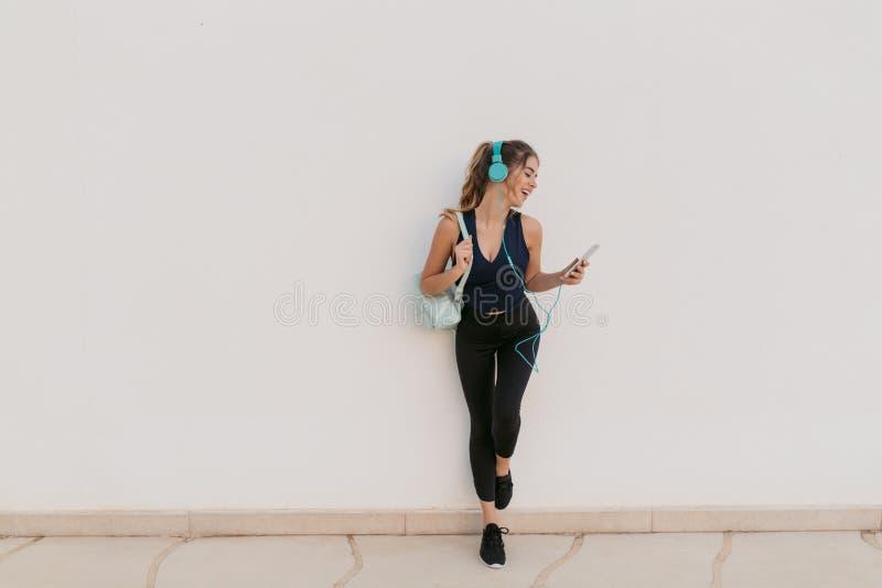 Jeune femme joyeuse de charme dans les vêtements de sport appréciant la causerie au téléphone, belle musique dans des écouteurs s photographie stock
