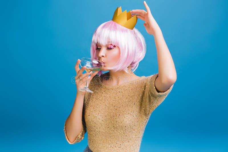Jeune femme joyeuse de portrait avec le champagne potable de coupe de cheveux rose avec fermé sur le fond bleu Maquillage de Brig images stock