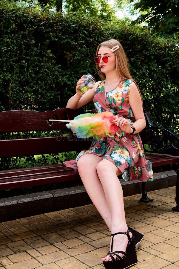 Jeune femme joyeuse heureuse avec le cocktail frais coloré de mojito de boissons de sucrerie de coton images stock