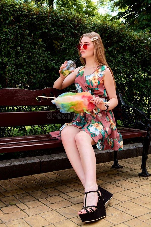 Jeune femme joyeuse heureuse avec le cocktail frais coloré de mojito de boissons de sucrerie de coton image stock
