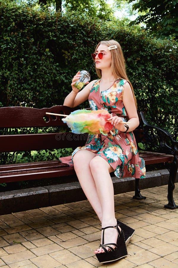Jeune femme joyeuse heureuse avec le cocktail frais coloré de mojito de boissons de sucrerie de coton photo libre de droits
