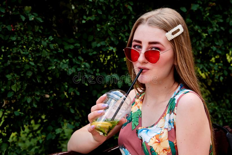 Jeune femme joyeuse heureuse avec le cocktail frais coloré de mojito de boissons de sucrerie de coton photos stock
