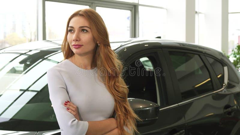 Jeune femme joyeuse souriant rêveusement se penchant sur une nouvelle voiture au concessionnaire photo stock