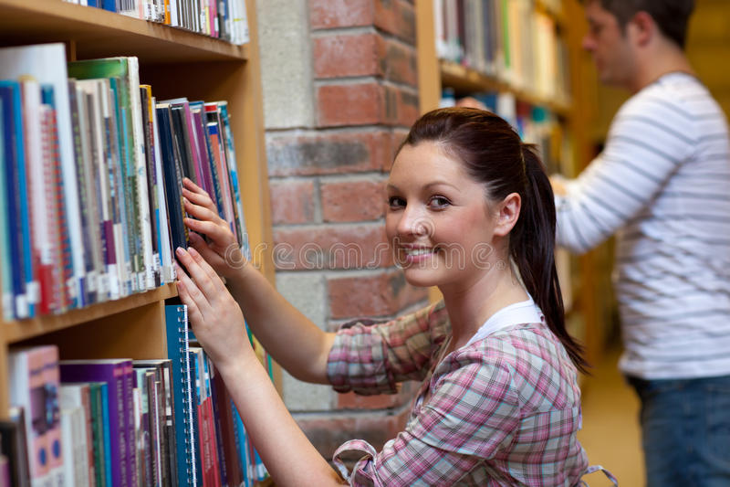 Jeune femme joyeux recherchant un livre photo stock