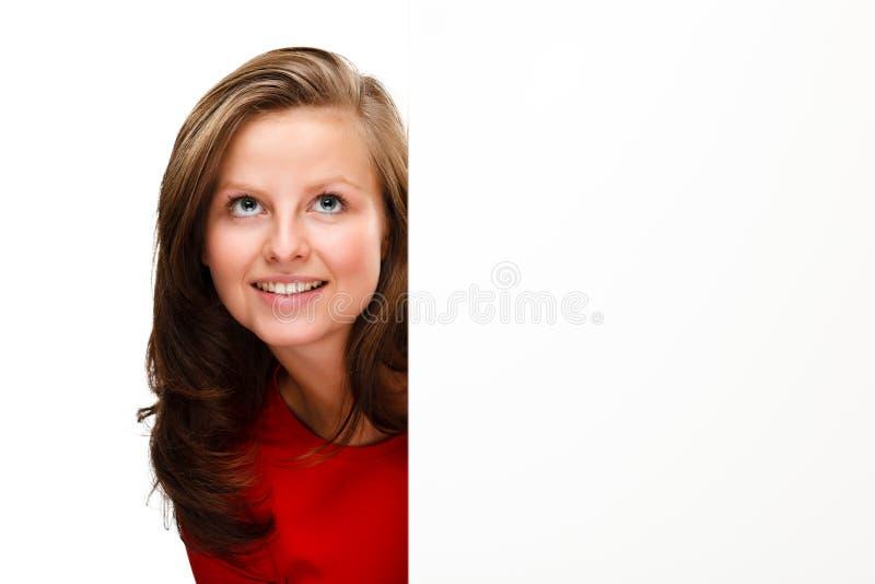 Jeune femme attirante derrière le conseil vide sur le fond blanc images stock