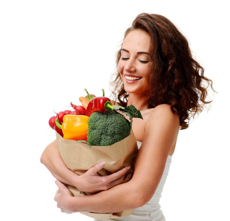 Jeune femme jugeant le panier de papier d'épicerie plein des légumes frais Concept sain de consommation de régime images libres de droits