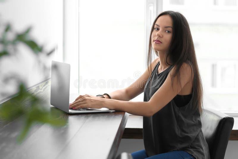 Jeune femme ? l'aide de l'ordinateur portable en caf? photo stock