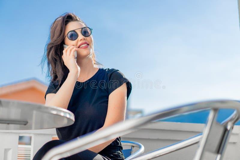 Jeune femme ?l?gante s'asseyant dehors sur le balcon et parlant par le t?l?phone portable photos stock
