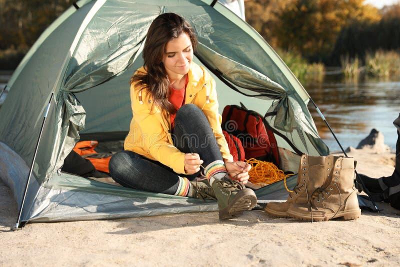 Jeune femme laçant la chaussure près de la tente dehors photos stock