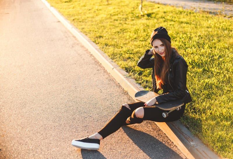 Jeune femme la belle et de mode s'assied avec une planche à roulettes sur le conseil photographie stock