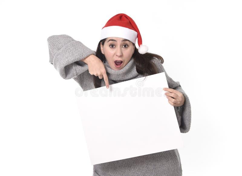 Jeune femme latine douce dans le chapeau de Santa Christmas dirigeant le panneau d'affichage vide photographie stock
