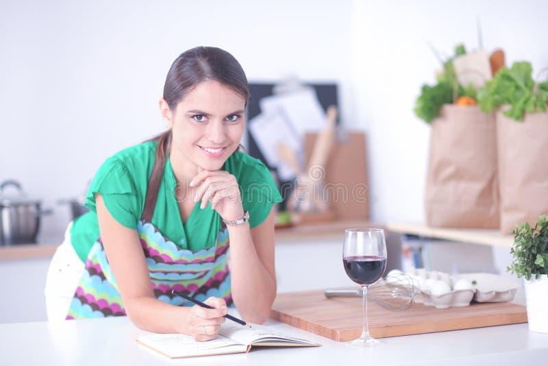 Jeune femme lisant un livre de recette dans la cuisine photographie stock