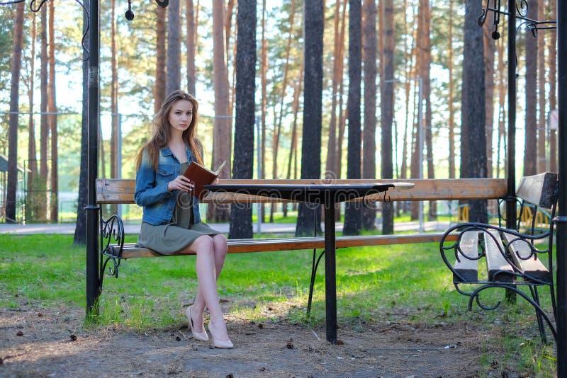 Jeune femme lisant un livre et détendant au parc image libre de droits