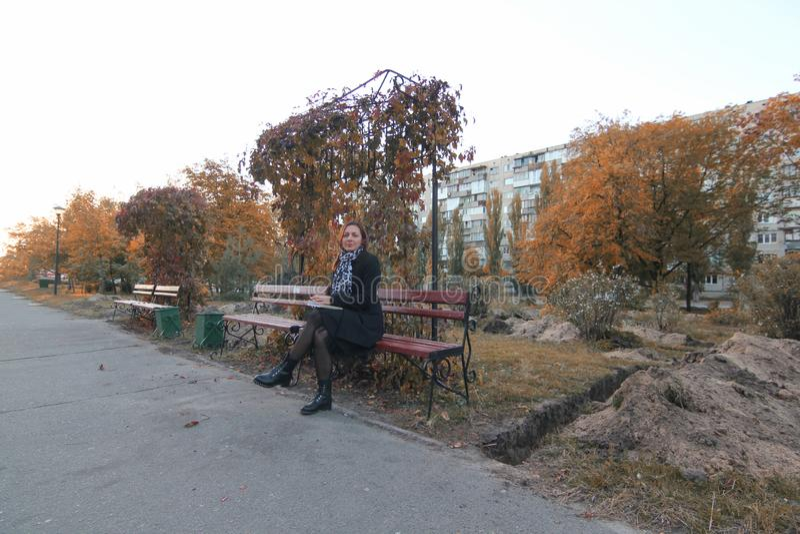 Jeune femme lisant un livre sur le banc en parc Joli jeune ?tudiant lisant un livre dehors sur le campus La fille image libre de droits