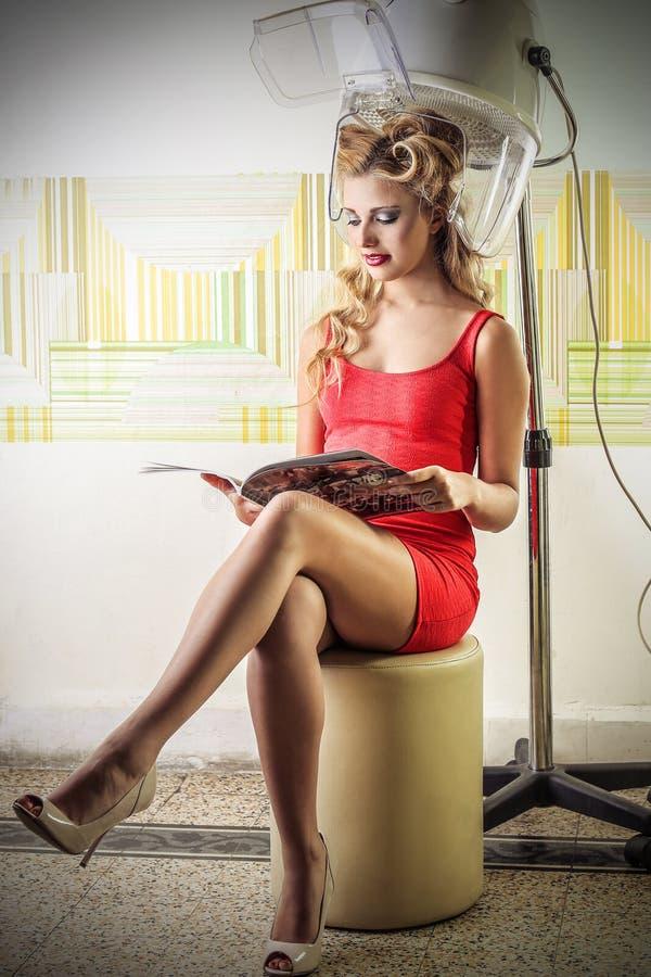 Jeune femme lisant un magazine au coiffeur photographie stock libre de droits