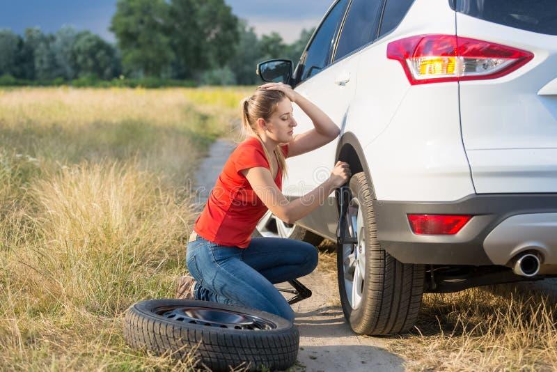 Jeune femme luttant pour changer le pneu de voiture plate sur la route de campagne photo stock