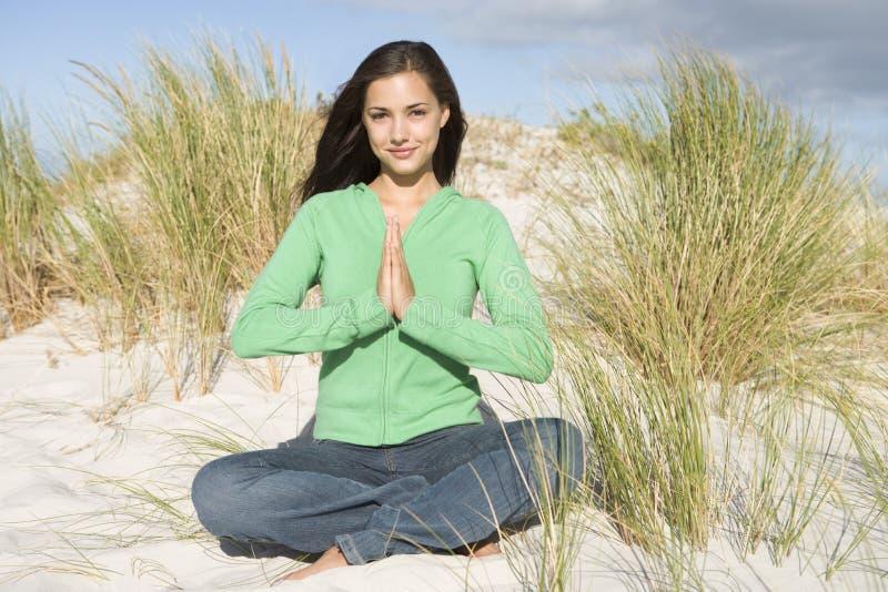 Jeune femme méditant parmi des dunes de sable image stock