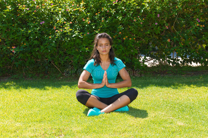 Jeune femme méditante dans la pose de lotus, posée dessus photos stock