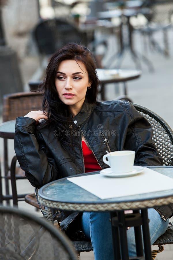 Jeune femme magnifique avec la tasse de café dans la rue de ville Croissant doux et une cuvette de café à l'arrière-plan Café pot photos libres de droits